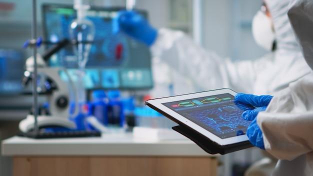 Rückansicht des wissenschaftlers im overall, der die virusentwicklung analysiert, die auf einem digitalen tablett schaut. team von mikrobiologen, die impfstoffentwicklung mit high-tech zur erforschung der behandlung von covid19 durchführen
