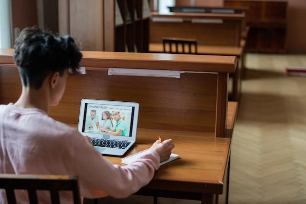 Rückansicht des zeitgenössischen college-studenten, der am schreibtisch vor dem laptop sitzt, während er entfernt auf der bildungswebsite lernt