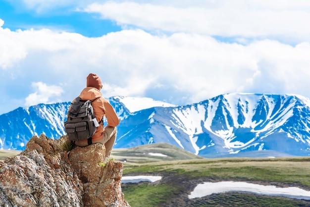 Rückansicht ein mann mit einem rucksack-wanderer sitzt auf dem gipfel des berges und schaut auf das tal der berge und genießt