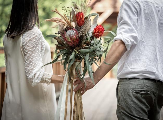 Rückansicht ein verliebtes paar, das einen blumenstrauß mit exotischen protea-blumen hält