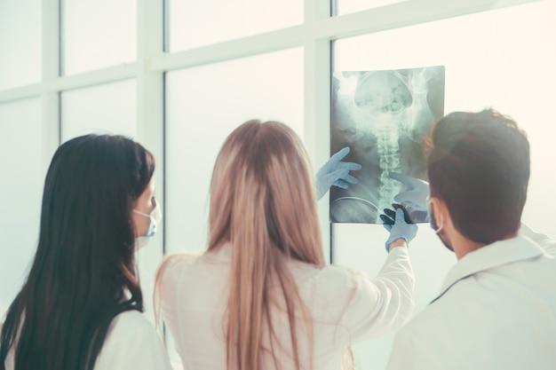 Rückansicht. eine gruppe von chirurgen, die über röntgenaufnahmen diskutieren. foto mit kopienraum