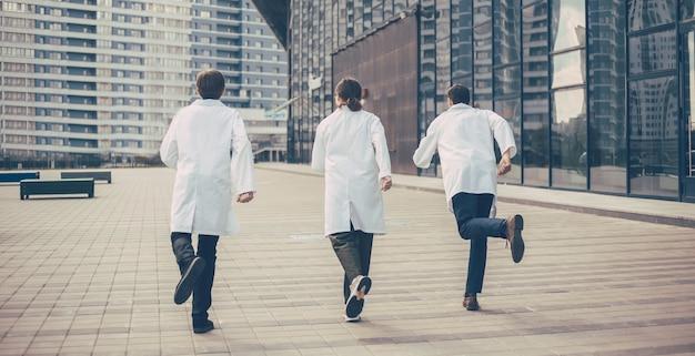Rückansicht. eine gruppe von rettungsärzten rennt, um nothilfe zu leisten. foto mit einem kopierraum.
