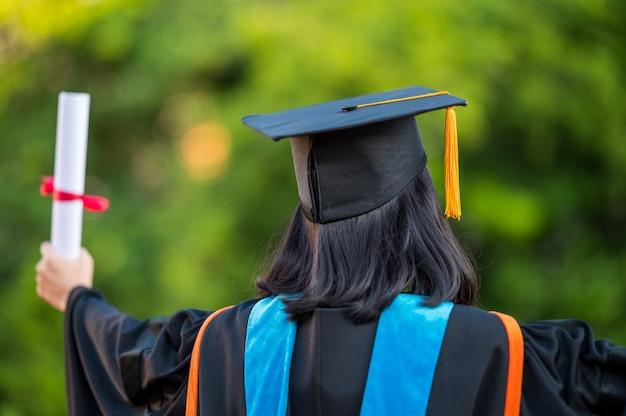 Rückansicht einer absolventin mit universitätsabschluss