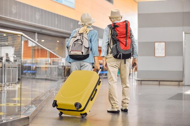 Rückansicht einer älteren dame mit einem trolley-koffer und einem mann mit bordkarte