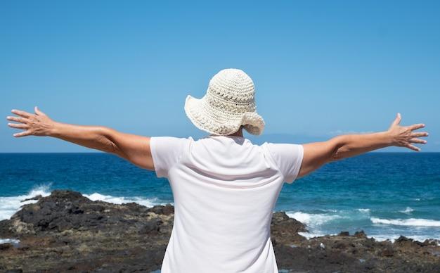 Rückansicht einer älteren frau mit weißem hut mit offenen armen, die blauen ozean und himmel umarmt. freiheit konzept. eine gesunde lebensweise. urlaub oder rente. gelassenheit und entspannung