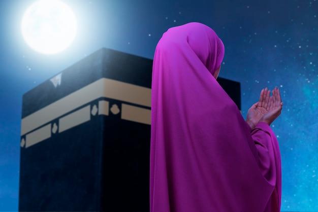 Rückansicht einer asiatischen muslimischen frau in einem schleier, die mit kaaba-ansicht und nachtszenenhintergrund steht und betet