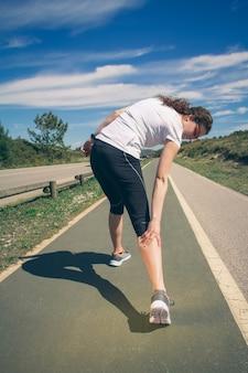 Rückansicht einer athletischen jungen frau mit sportbekleidung, die durch einen muskelkrampf bei einem training schmerzen in ihrer wade erleidet. konzept für sportverletzungen.