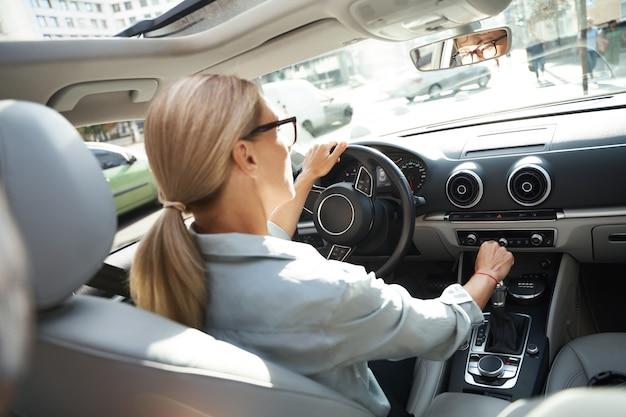 Rückansicht einer erfolgreichen kaukasischen geschäftsfrau, die ihr modernes auto durch die stadt fährt