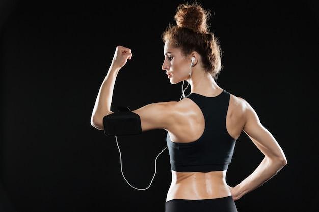 Rückansicht einer fitnessfrau, die ihren bizeps zeigt