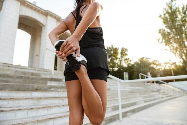 Rückansicht einer fitnessfrau in kopfhörern, die sich strecken