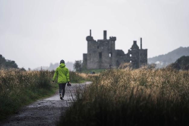 Rückansicht einer fotografin vor kilchurn castle, schottland