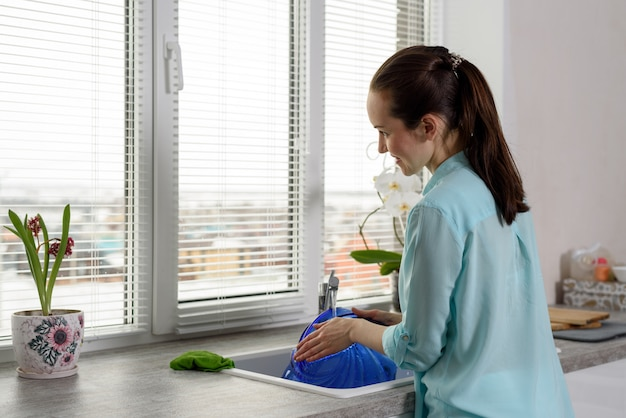 Rückansicht einer frau beim abwasch in der küche vor dem fenster
