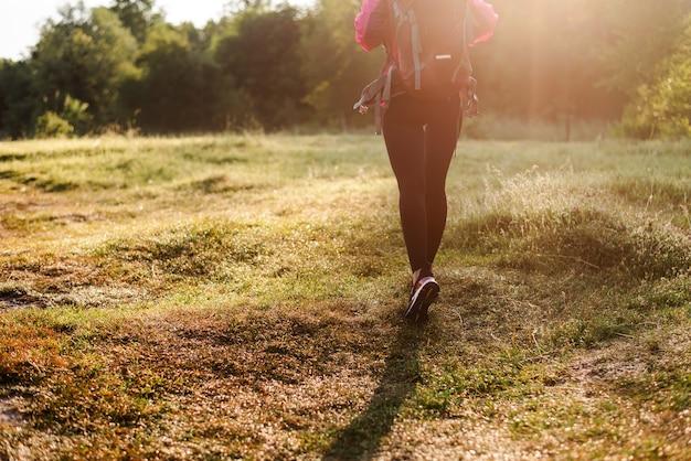 Rückansicht einer frau, die mit rucksack auf der grünen wiese in der nähe des waldes geht. mädchen tragen sportkleidung und rosa jacke. konzept der erholung und des tourismus in der natur. sommer. sonniger tag