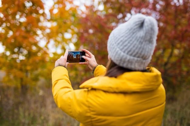 Rückansicht einer frau, die mit smartphone foto des herbstwaldes macht