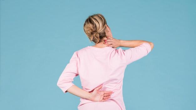 Rückansicht einer frau, die unter rückenschmerzen und schulterschmerzen leidet
