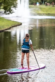Rückansicht einer frau in schwimmweste, die auf einem paddleboard steht