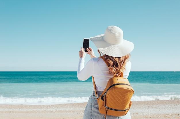 Rückansicht einer frau mit smartphone und blick auf den strand