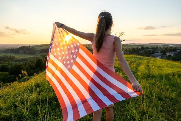 Rückansicht einer glücklichen frau mit der nationalflagge der usa, die bei sonnenuntergang im freien steht. positive frau, die den unabhängigkeitstag der vereinigten staaten feiert. internationaler tag des demokratiekonzepts.