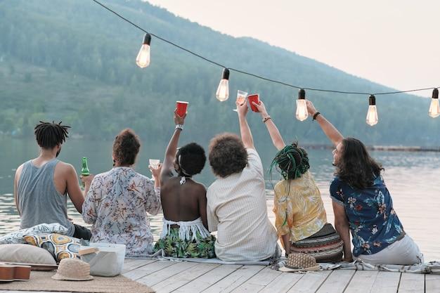 Rückansicht einer gruppe von freunden, die mit einem glas bier anstoßen und ihre sommerferien feiern, während sie auf einem pier sitzen