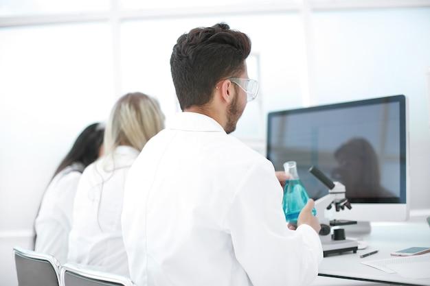 Rückansicht einer gruppe von wissenschaftlern, die in einem modernen labor arbeiten