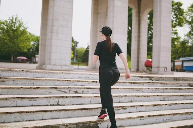Rückansicht einer jungen athletischen, starken brünetten frau in schwarzer uniform und mütze, die sportübungen macht, aufwärmen vor dem laufen auf treppen im stadtpark im freien klettern