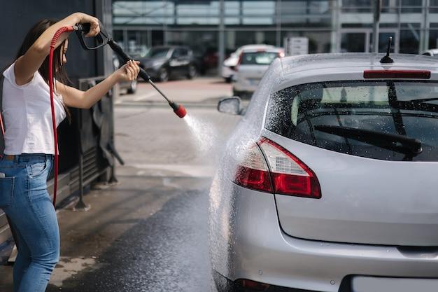 Rückansicht einer jungen frau, die ihr auto auf einem selbstbedienungsauto putzt, das mit einem weißen strahlsprüher wäscht