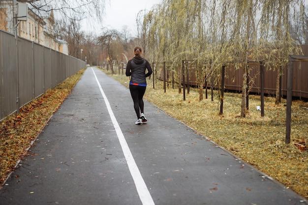 Rückansicht einer jungen frau, die im herbstpark entlang des radwegs joggt