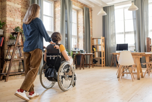 Rückansicht einer jungen frau, die mit ihrem behinderten kollegen oder freund rollstuhl schiebt, während sie sich um sie kümmert und hilft, sich im haus zu bewegen