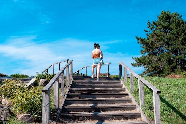 Rückansicht einer jungen frau in kurzen hosen beim treppensteigen in einem sommerpark an einem sonnigen tag.