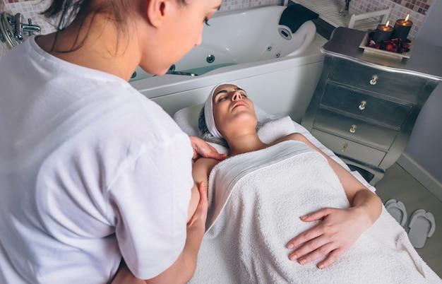 Rückansicht einer massagetherapeutin, die in einem klinischen zentrum eine lymphdrainagemassage einer jungen frau durchführt. medizin-, gesundheits- und schönheitskonzept.