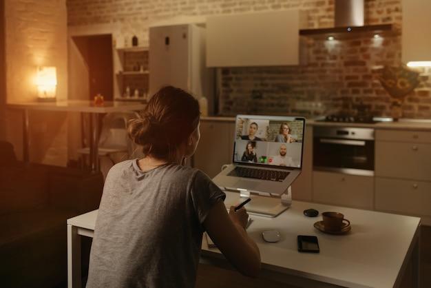 Rückansicht einer mitarbeiterin, die remote arbeitet und mit ihren kollegen in einer videokonferenz auf einem laptop von zu hause aus spricht.