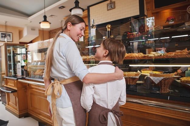 Rückansicht einer mutter und eines sohnes, die in ihrer familienbäckerei arbeiten und sich gegenseitig anlächeln