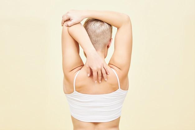 Rückansicht einer nicht erkennbaren jungen frau mit einem jungenhaften kurzen haarschnitt, der die arme hinter ihrem rücken streckt und die beweglichkeit des schultergelenks und der sich öffnenden brust verbessert. menschen-, sport- und fitnesskonzept