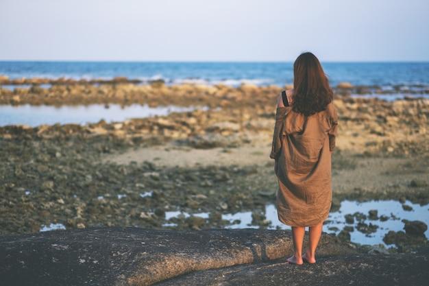 Rückansicht einer schönen asiatischen frau, die allein am strand an der küste steht