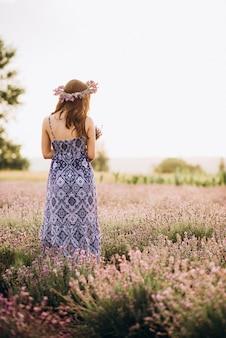 Rückansicht einer schönen frau in einem langen kleid und einem kranz im lavendelfeld bei sonnenuntergang.