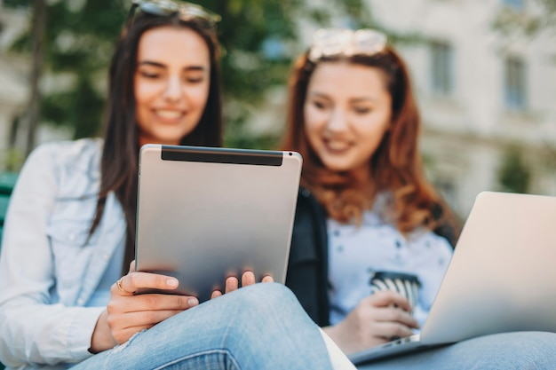 Rückansicht einer tablette, die von zwei reizenden mädchen verwendet wird, die lächelnd auf einer bank draußen im park sitzen.