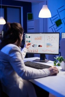 Rückansicht einer überwältigten frau, die nachts vor dem computer arbeitet, notizen zu notebook-jahresberichten schreibt, die finanzielle frist überprüft. fokussierter manager mit drahtlosem technologienetzwerk
