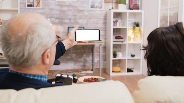 Rückansicht eines älteren ehepaares, das beim sitzen auf dem sofa im wohnzimmer auf das telefon mit grünem bildschirm schaut.
