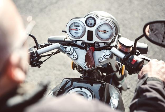 Rückansicht eines älteren mannes, der das motorrad auf der straße steuert