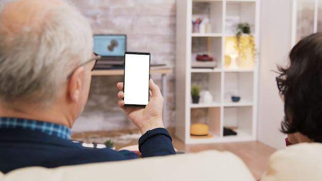 Rückansicht eines älteren paares, das telefon mit grünem bildschirm hält.