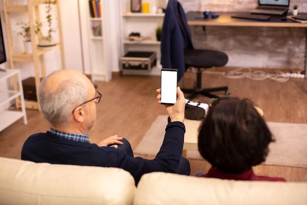 Rückansicht eines älteren rentnerehepaares, das ein smartphone mit weißem isoliertem bildschirm betrachtet.