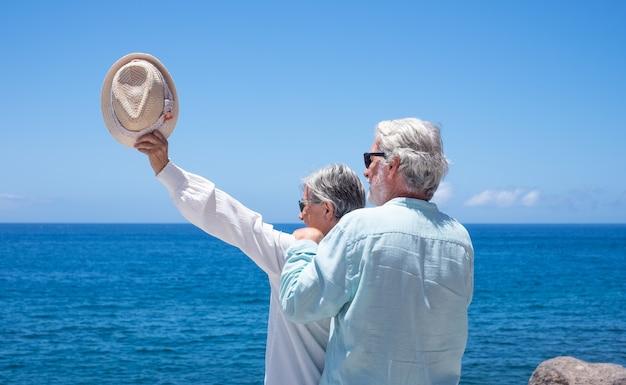 Rückansicht eines älteren weißhaarigen paares, das den horizont über dem meer betrachtet. glückliche rentner, die am strand stehen und die sommerferien genießen