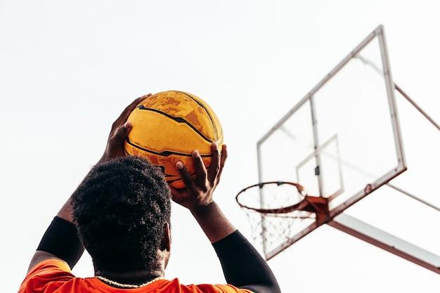 Rückansicht eines afroamerikanischen schwarzen jungen, der bereit ist, den ball in den korb zu schießen.