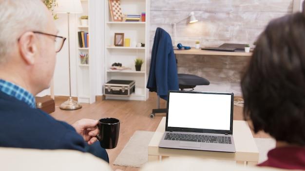 Rückansicht eines alten ehepaares, das am laptop mit grünem bildschirm winkt.