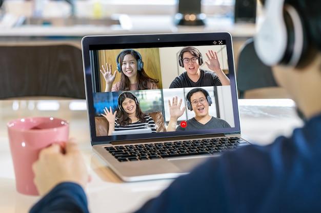 Rückansicht eines asiatischen geschäftsmannes, der in einer videokonferenz hallo mit teamwork-kollegen sagt
