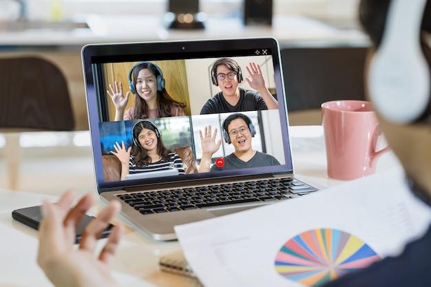 Rückansicht eines asiatischen geschäftsmannes sagt hallo mit teamwork-kollegen in videokonferenz