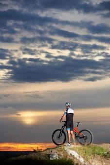 Rückansicht eines athletischen mannes mit einem fahrrad, das den abendhimmel und die schöne sonne bei sonnenuntergang auf einem berg mit einer atemberaubenden landschaft von hügeln in der ferne genießt.