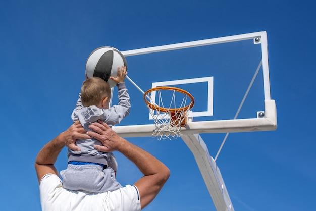 Rückansicht eines enkels, der auf der schulter seines großvaters sitzt und einen basketball in einen reifen wirft