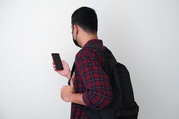 Rückansicht eines erwachsenen asiatischen mannes, der eine medizinische schutzmaske und einen rucksack trägt und auf sein mobiltelefon schaut