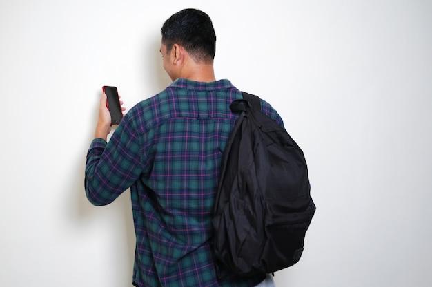 Rückansicht eines erwachsenen asiatischen mannes mit rucksack, der auf sein handy schaut